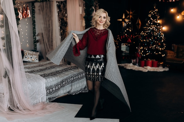 Charming blonde woman envelopes herself in grey plaid sitting on a bed before a christmas tree Free Photo