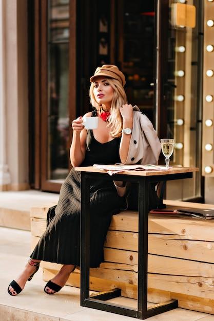 レストランの横にある木製のベンチに座って、お気に入りの飲み物を楽しんでいる魅力的な金髪の女性。コーヒーを飲み、誰かを待っているコートとキャップの壮大な女の子の屋外の肖像画。 無料写真