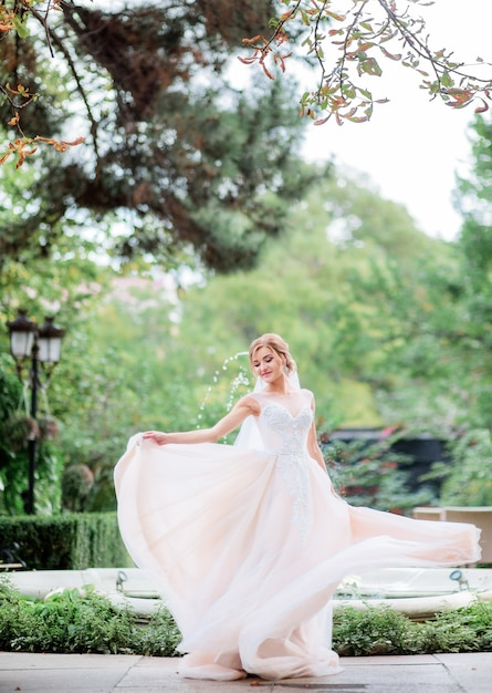 Charming bride in a peach dress whirls before fountain in the garden Free Photo