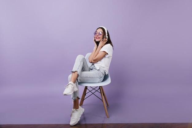 Очаровательная кавказская дама в винтажных джинсах, слушая музыку. портрет блаженной дамы брюнет носит наушники. Бесплатные Фотографии