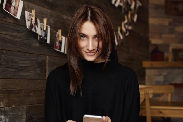Affascinante donna caucasica con capelli color cioccolato e sorriso misterioso Foto Gratuite