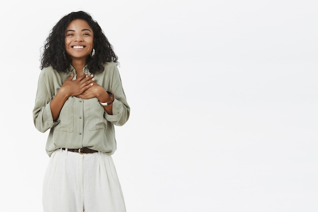 Charming charismatic and delighted cute african american with curly hair in stylish outfit feeling grateful and happy Free Photo
