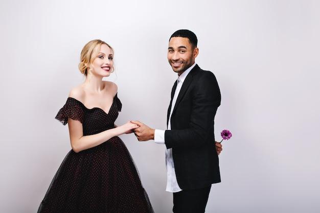 Очаровательная влюбленная пара празднует день святого валентина. привлекательная женщина в роскошном вечернем платье, элегантный красавец в смокинге с цветком за спиной. любовь, улыбка, потаскуха. Бесплатные Фотографии