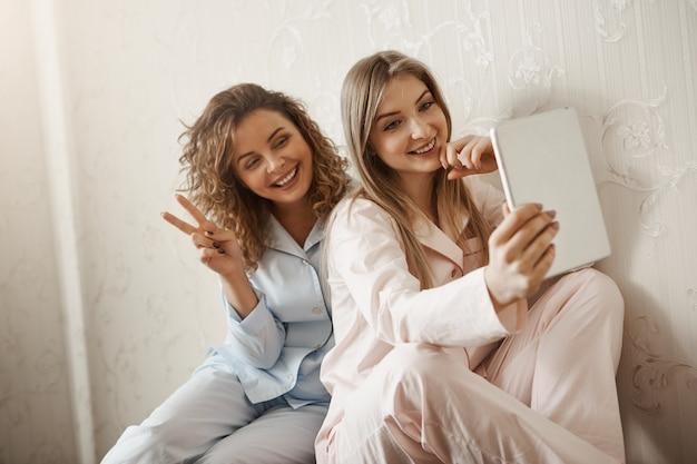 デジタルタブレットを使用してママとselfieを取るパジャマの魅力的な娘 無料写真