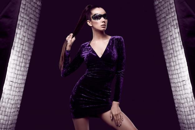 Affascinante donna bruna elegante in abito viola e maschera di paillettes Foto Gratuite