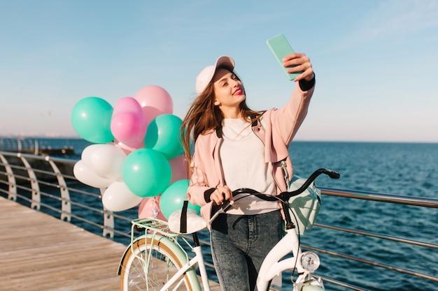 Affascinante ciclista femminile in un berretto rosa e giacca a vento sorridente e prendendo selfie sullo sfondo del mare. adorabile ragazza bruna con bicicletta bianca e palloncini colorati festa divertendosi accanto all'oceano. Foto Gratuite