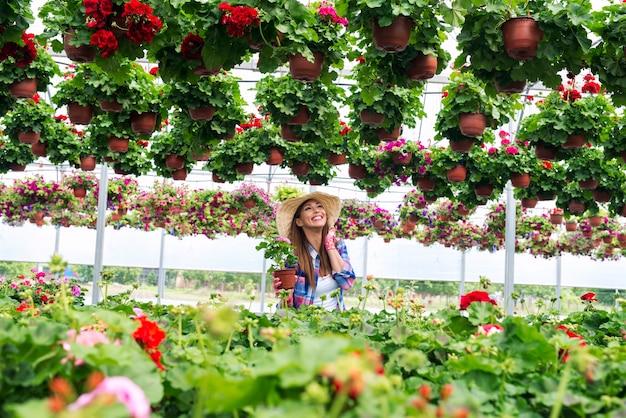 温室で花の世話をし、彼女の仕事を楽しんでいる魅力的な女性の花屋 無料写真