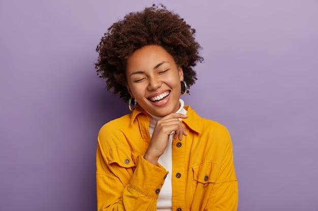 Affascinante donna femminile ride di felicità, tocca il mento e sorride positivamente, si sente sollevata e gioiosa, indossa una giacca gialla alla moda, isolata su sfondo viola. Foto Gratuite
