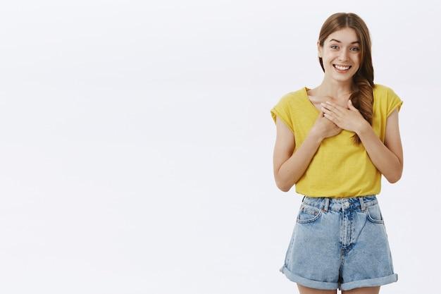 Очаровательная дружелюбная и милая взрослая высокая девушка в желтой футболке и шортах, держащая ладони на груди и улыбающаяся с чувством благодарности и признательности Бесплатные Фотографии