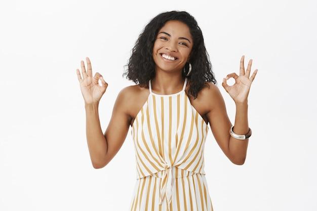 魅力的なフレンドリーな外観の浅黒い肌の女性で、幸せと喜びから微笑んでいる巻き毛の髪型で、大丈夫または優れたジェスチャーを示す頭を傾けます 無料写真