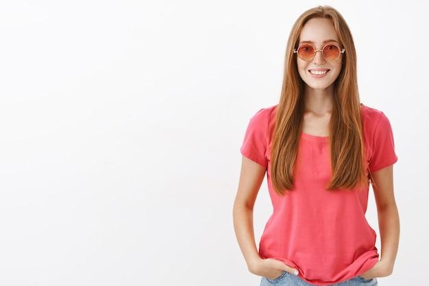Affascinante ragazza hippie dall'aspetto amichevole con i capelli rossi e le lentiggini che si tengono per mano in tasca e sorridono casualmente indossando occhiali da sole rosa alla moda e camicetta sopra il muro bianco Foto Gratuite