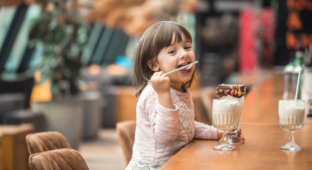 魅力的な面白い女の子がミルクセーキを飲む 無料写真
