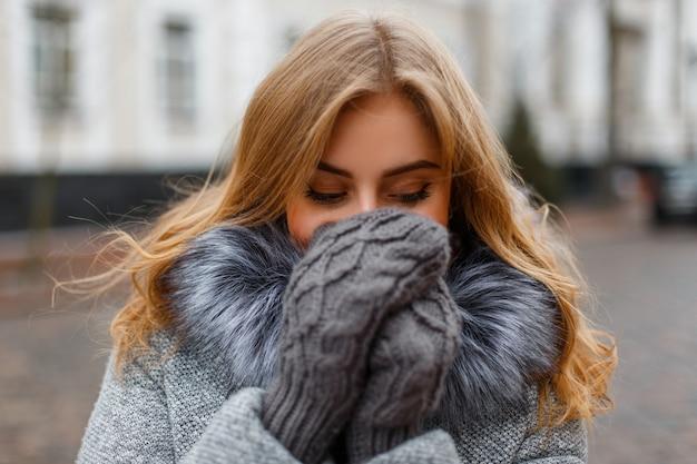 魅力的な面白い若い女性は笑って、ヴィンテージの建物のニットミトンで彼女の手で彼女の顔を覆います。陽気な素敵な女の子。 Premium写真