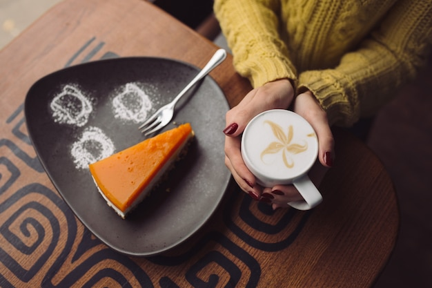 Charming girl drinking cappuccino and eating cheesecake Free Photo