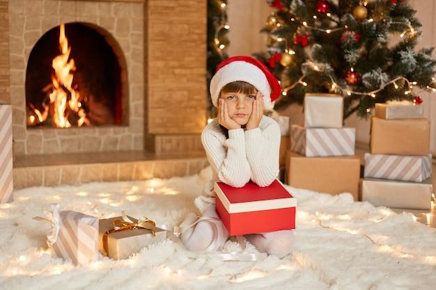 선물 상자와 함께 바닥에 앉아 뺨에 손바닥을 유지하는 매력적인 소녀는 지루해 보입니다. 프리미엄 사진