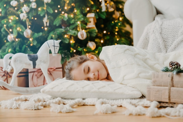 Charming girl sleeps on soft white pillow on floor against decorated new year tree, has pleasant dreams, surrounded with toy horse and gift boxes. children, rest and winter holidays concept. Premium Photo