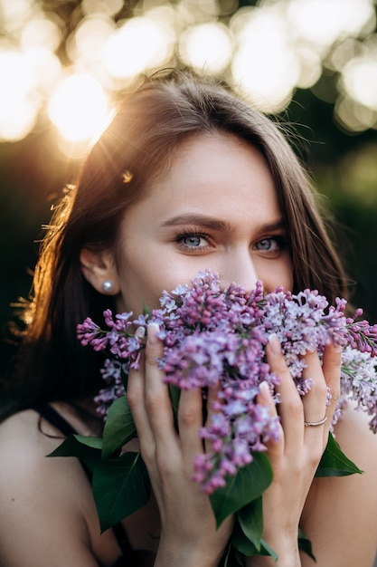 The charming girl stands in the park and keeps a bouquet Free Photo
