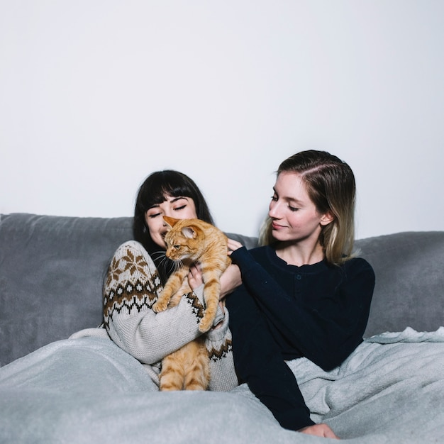 Charming girls cuddling with cat on couch Free Photo