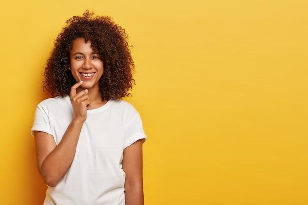 아프로 머리를 가진 매력적인 십대 소녀, 부드럽게 미소 짓고, 자연의 아름다움을 가지고 있으며, 기분이 좋으며, 주말 동안 멋진 시간을 즐기고, 노란색에 고립 된 흰색 캐주얼 의류를 입습니다. 무료 사진