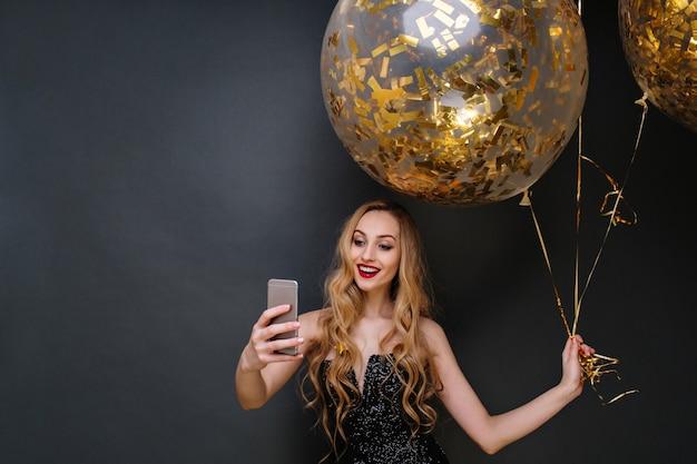 黒の豪華なドレスを着た魅力的な楽しい若い魅力的な女性。長い巻き毛のブロンドの髪が、金色のティンセルでいっぱいの大きな風船で自分撮りをしています。現代のパーティーを祝う。 無料写真