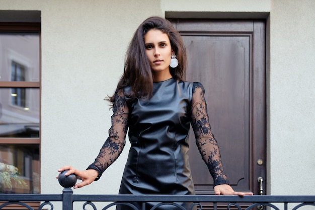 Charming lady in short leather dress with lace sleeves outdoor Premium Photo
