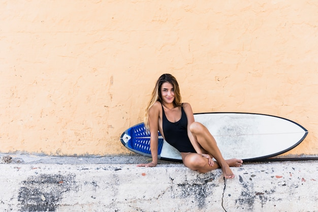 Charming lady with surfboard sitting near building Free Photo