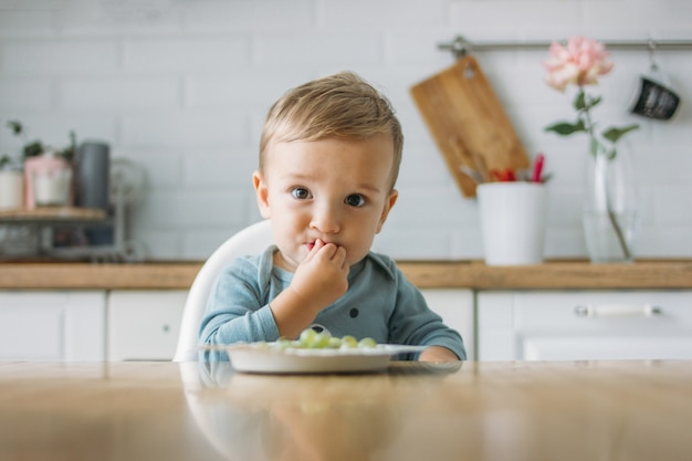 Charming little baby boy eating first food green grape at the bright kitchen at home Premium Photo