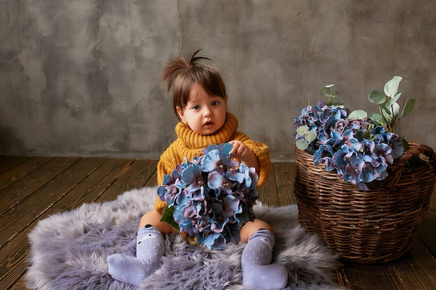 Charming little baby-girl in orange sweater explores blue hydrangeas sitting on warm blanket Free Photo