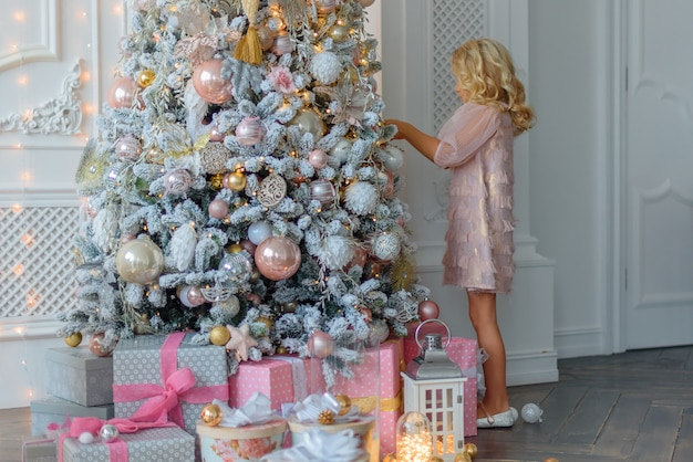 Charming little blonde with curly hair in a beautiful pink dress, adorns the christmas tre Premium Photo