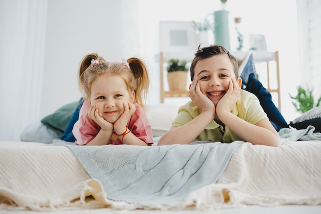 Charming little boy and girl lie on the bed
