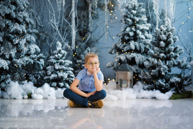 Charming little boy is sitting at home, snowy winter decorated tree on background Premium Photo