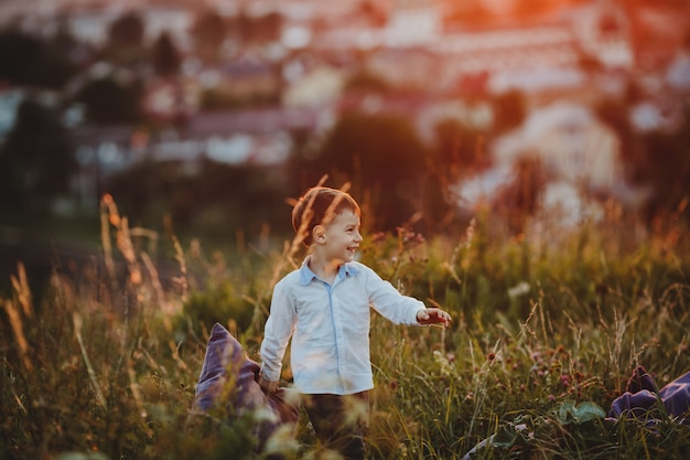Charming little boy walks with a pillow across green lawn Free Photo