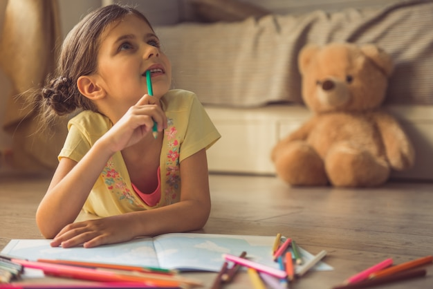 Charming little girl is drawing, looking away. Premium Photo