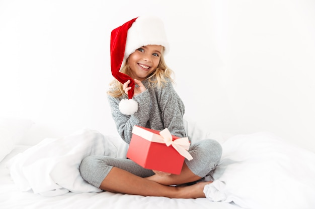 Charming little girl touching her santa's hat holding gift box,  while sitting on bed Free Photo