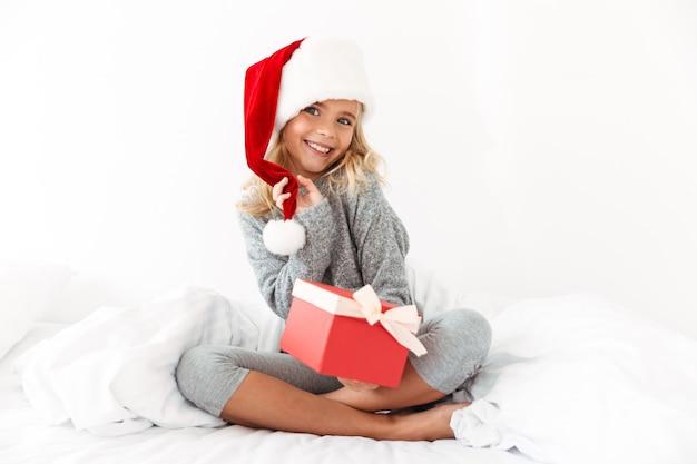 Очаровательная маленькая девочка трогает шляпу своего санты, держа подарочную коробку, сидя на кровати Бесплатные Фотографии