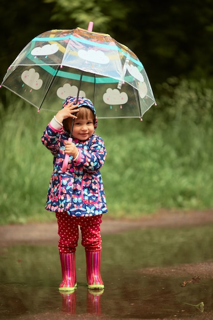 Charming little girl with umbrella has fun standing in gumboots in the pool after rain Free Photo