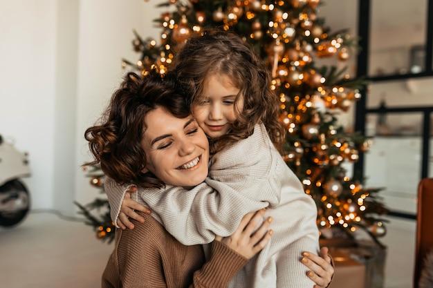 곡선이 그녀의 작은 딸과 함께 포옹하고 크리스마스와 새해를 축하하는 매력적인 사랑스러운 백인 여자 무료 사진