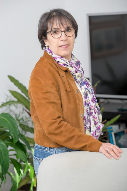 Charming mature woman with brown jacket and glasses Premium Photo