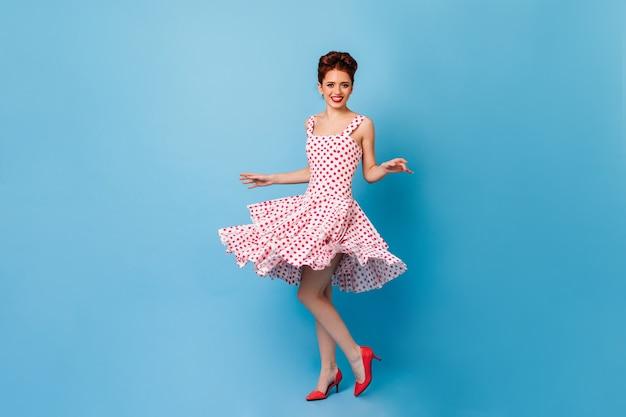 誠実な笑顔でカメラを見ている魅力的なピンナップ女性。青い空間で踊る水玉模様のドレスを着た女性モデルのスタジオショット。 無料写真