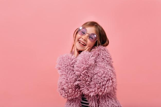 Очаровательная красивая девочка 6 лет в меховом фиолетовом мехе и круглых очках позирует со счастливыми эмоциями Бесплатные Фотографии