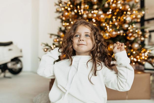 Очаровательная симпатичная маленькая девочка с кудрями в белой одежде, улыбаясь впереди на елке с огнями Бесплатные Фотографии