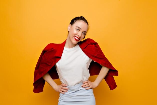 黄色の壁に赤いジャケット、白いtシャツ、青いスカートを着てポーズをとって素敵な笑顔で魅力的なかなり若い女性。本当の感情を持つ素敵な女の子 無料写真