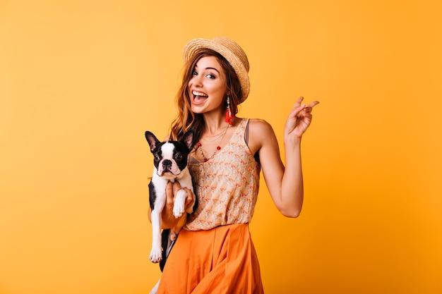 フレンチブルドッグを保持しているヴィンテージの帽子の魅力的な赤毛の女の子。子犬と黄色でポーズをとって驚いた白人女性の屋内の肖像画。 無料写真