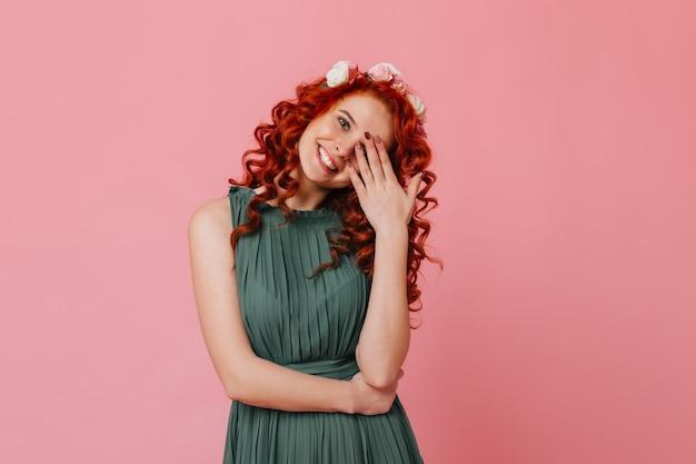 頭に花をつけた魅力的な赤毛の少女は、優しく微笑んで顔を手で覆います。ピンクのスペースに緑の衣装で女性の肖像画。 無料写真