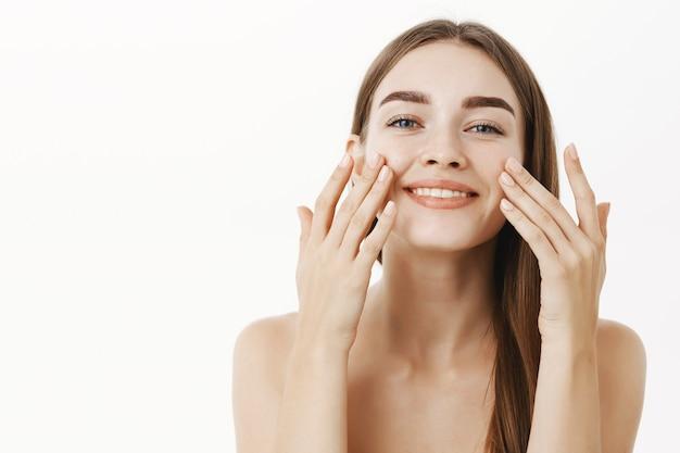 魅力的なリラックスした穏やかな若い女性の指で顔に顔のクリームを適用し、広く完璧な感じ、肌の世話をして笑顔の美容手順を作る 無料写真
