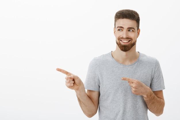 Affascinante giovane maschio soddisfatto e felice con barba e baffi sorridente deliziato con denti bianchi perfetti che punta e che guarda a sinistra soddisfatto e divertito sul muro bianco Foto Gratuite