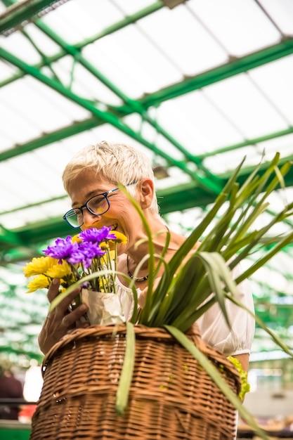 Charming senior woman buying flowers on market Premium Photo