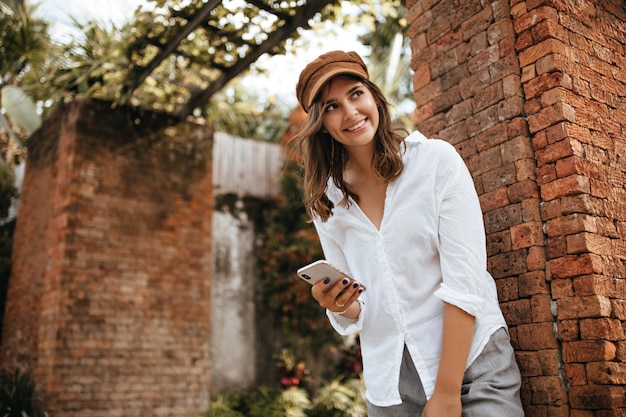 Charming short-haired girl leaned on wall of old brick building, smiling and holding phone. snapshot of woman in gray pants and white blouse. Free Photo