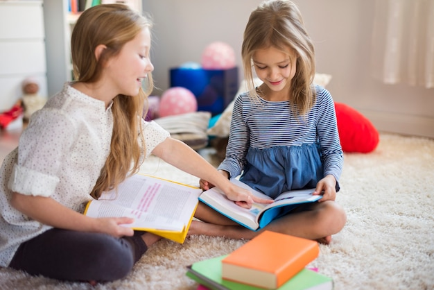 Charming sisters browsing their adventure books Free Photo