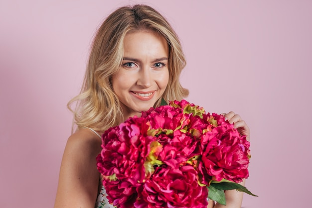 Charming smiling blonde young woman holding flower bouquet against pink backdrop Free Photo